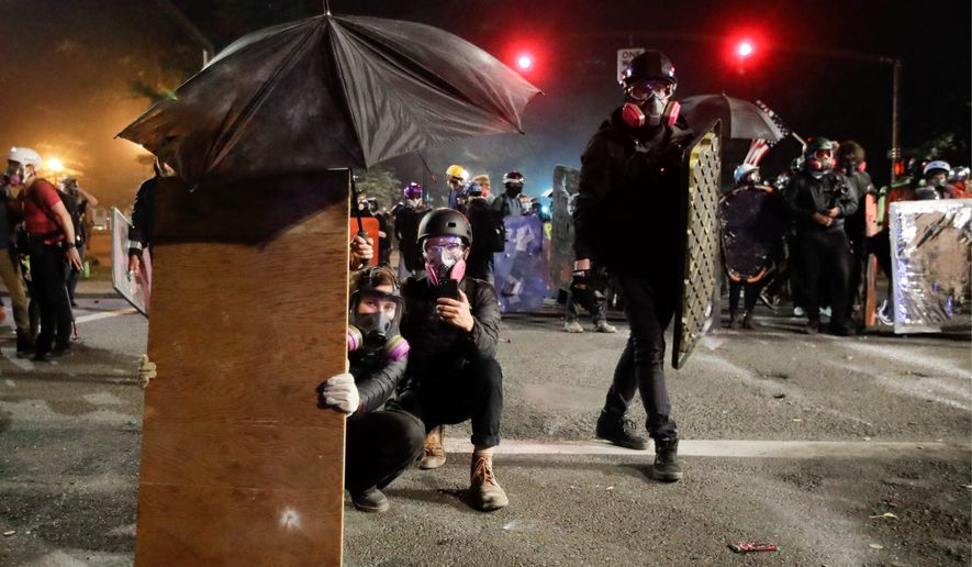 Demonstrators in Portland, Oregon, shielded themselves from advancing federal officers and used leaf blowers to blow back tear gas during a nightly standoff this summer. Police made a record 59 arrests in one day this weekend. (Associated Press)