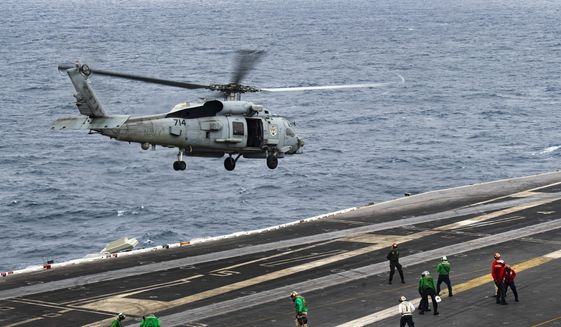 In this photo released by the U.S. Navy, an MH-60R Seahawk helicopter takes off from the USS Nimitz in the Arabian Sea on Aug. 27, 2020. The U.S. Navy searched through the night into the morning of Monday, Sept. 7, 2020, for a sailor who went missing from the aircraft carrier USS Nimitz during its patrol of the northern Arabian Sea amid tensions with Iran. (Mass Communication Specialist 3rd Class Dalton Reidhead/U.S. Navy via AP)