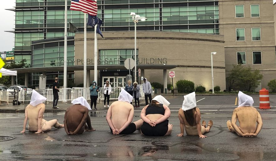 """Naked protesters, wearing """"spit hoods"""" in reference to the killing of Daniel Prude, demonstrate outside Rochester's Public Safety Building in Rochester, N.Y., Monday, Sept. 7, 2020. (Tracy Schuhmacher/Democrat & Chronicle via AP)"""