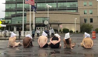 "Naked protesters, wearing ""spit hoods"" in reference to the killing of Daniel Prude, demonstrate outside Rochester's Public Safety Building in Rochester, N.Y., Monday, Sept. 7, 2020. (Tracy Schuhmacher/Democrat & Chronicle via AP)"
