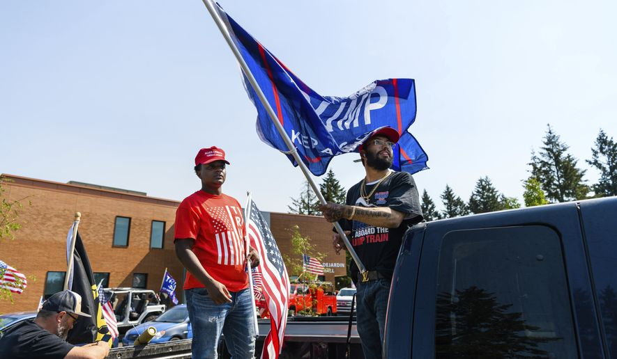 """Friends Darrin Gantt, 20, left, and Stevan Garcia, 24, attend their second Trump rally at the """"Oregon for Trump 2020 Labor Day Cruise Rally"""" at Clackamas Community College in Oregon City, Ore., Monday, Sept. 7, 2020. (AP Photo/Michael Arellano)"""