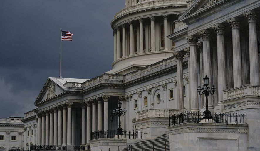 In this Aug. 3, 2020, file photo, dark clouds and heavy rain sweep over the U.S. Capitol in Washington. (AP Photo/J. Scott Applewhite) **FILE**