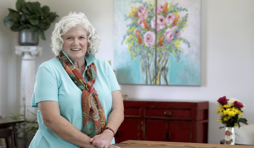 In this Friday, Aug. 14, 2020, photo, elementary art school teacher Joey Kiernan poses for a picture in front of one of her paintings hanging in her home in Billings, Mont. (Casey Page/The Billings Gazette via AP)