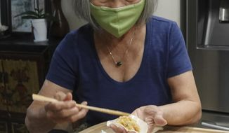 Shirley Shea makes dumplings at her home in Fort Lauderdale, Fla., Wednesday, Aug. 19, 2020. The tapestry of pork dumplings on Calvin Shea's Instagram feed has been popular in quarantine during the coronavirus pandemic. But not nearly as popular as his 80-year-old mom, Shirley. What started as a way to renew their relationship after living apart for decades has turned, practically overnight, into an all-consuming dumpling business. (Joe Cavaretta/South Florida Sun-Sentinel via AP)