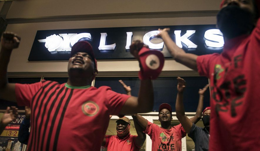 """Economic Freedom Fighters (EFF) supporters protest outside a Clicks store in Soweto, Johannesburg, Monday, Sept. 7 2020 calling for the closure of the stores around the country. The chain store posted an advertisement on their website that negatively described natural Black hair labelled as being """"Dry and Damaged"""" and """"Frizzy and Dull"""", while white people's hair was called """"Fine and Flat"""" and """"Normal"""". (AP Photo/Shiraaz Mohamed)"""