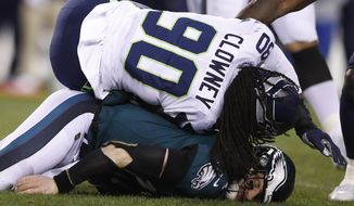 FILE - In this Jan. 5, 2020, file photo, Philadelphia Eagles' Carson Wentz, bottom, is hit by Seattle Seahawks' Jadeveon Clowney (90) during the first half of an NFL wild-card playoff football game in Philadelphia. The Tennessee Titans have agreed to terms with three-time Pro Bowl linebacker Clowney on a one-year contract. The Titans did not announce the terms Sunday, Sept. 6, 2020. (AP Photo/Julio Cortez, File)