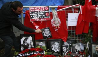 FILE - In this Wednesday, Jan. 4, 2017 file photo, a man adjusts a victim's photograph displayed with floral tributes and Turkish flags, outside the Reina night club following the New Year's day attack, in Istanbul. A Turkish court has on Monday, Sep. 7, 2020 sentenced an Islamic State militant to life in prison over the New Year's Eve attack on a nightclub in Istanbul that left 39 people dead in 2017. Albulkadir Masharipov of Uzbekistan was charged with membership in a terror group, murder and attempting to overthrow the constitutional order, among other charges. (AP Photo/Emrah Gurel, file)