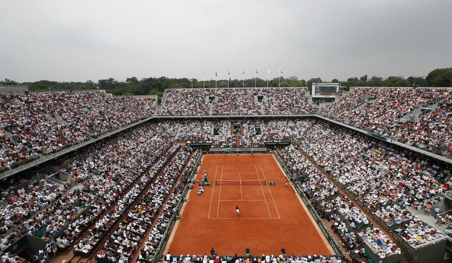 FILE - In this June 10, 2018 file photo, the crowd watch Austria's Dominic Thiem serving to Spain's Rafael Nadal during the men's final match of the French Open tennis tournament at the Roland Garros stadium,in Paris. Spectators will be allowed at the French Open later this month despite the growing number of coronavirus cases in the country, organizers said on Monday as they unveiled the health protocols for the clay-court Grand Slam tournament. The event will take place at Roland Garros stadium in western Paris from Sept. 27 after being postponed from its May date due to the pandemic. (AP Photo/Christophe Ena, File)