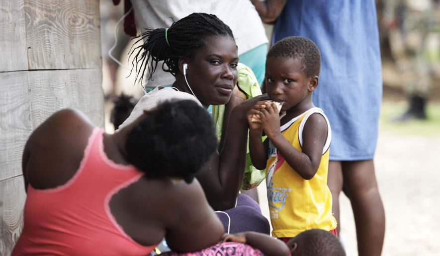 Women and children sit idle at a migrant camp amid the new coronavirus pandemic in Lajas Blancas, Darien province, Panama, Saturday, Aug. 29, 2020. In Lajas Blancas, the migrants did not wear masks or practice social distancing, but Panama's Public Security Minister Juan Pino said there have not been more than 10 infections among the migrants. (AP Photo/Arnulfo Franco) **FILE**
