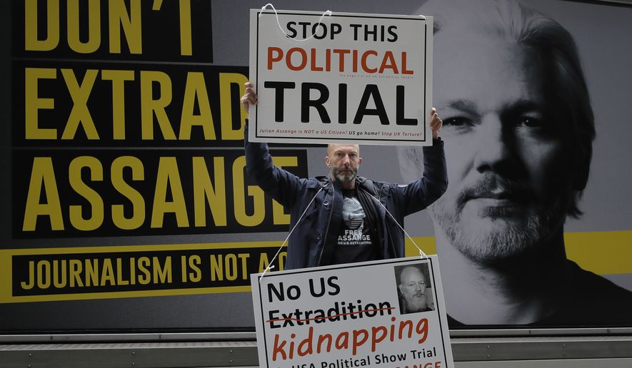 A demonstrator holds placards near the Central Criminal Court Old Bailey in London, Tuesday, Sept. 8, 2020. (AP Photo/Kirsty Wigglesworth)