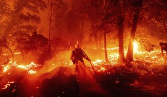 A firefighter battles the Creek Fire as it threatens homes in the Cascadel Woods neighborhood of Madera County, Calif., on Monday, Sept. 7, 2020. (AP Photo/Noah Berger)