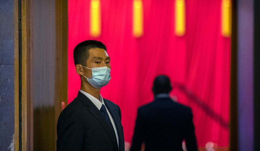 A security official wearing a face mask stands guard before an event to honor some of those involved in China's fight against COVID-19 at the Great Hall of the People in Beijing, Tuesday, Sept. 8, 2020. Chinese leader Xi Jinping is praising China's role in battling the global coronavirus pandemic and expressing support for the U.N.'s World Health Organization, in a repudiation of U.S. criticism and a bid to rally domestic support for Communist Party leadership. (AP Photo/Mark Schiefelbein) **FILE**