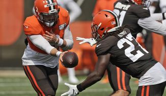 Cleveland Browns quarterback Baker Mayfield, left, hands the ball off to running back Kareem Hunt during practice at the NFL football team's training camp facility, Thursday, Aug. 27, 2020, in Berea, Ohio. (AP Photo/Tony Dejak)