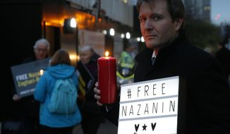 FILE -- In this Jan. 16, 2017 file photo, Richard Ratcliffe husband of imprisoned British-Iranian dual national Nazanin Zaghari-Ratcliffe, poses during an Amnesty International led vigil outside the Iranian Embassy in London. On Tuesday, Sept. 8, 2020, Iran's state TV, citing unnamed official, said Zaghari-Ratcliffe faces a new charge but did not elaborate. Zaghari-Ratcliffe had been released from prison due to the coronavirus pandemic after serving nearly all of her five-year sentence. She was arrested during a holiday with her toddler daughter in April 2016. (AP Photo/Alastair Grant, File)