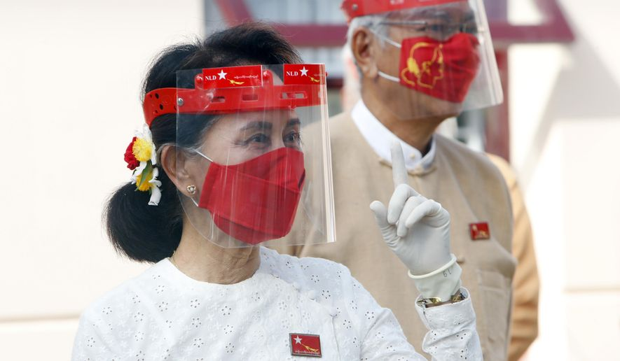 Myanmar leader Aung San Suu Kyi gestures while wearing a face shield, mask and gloves during a flag-raising ceremony to mark the first day of election campaigning at the National League for Democracy party's temporary headquarters in Naypyitaw, Myanmar on Tuesday, Sept. 8, 2020. Myanmar holds a general election on Nov. 8 and began a 60-day election campaign period Tuesday, which may be disrupted due to a resurgence of the coronavirus. (AP Photo/Aung Shine Oo)