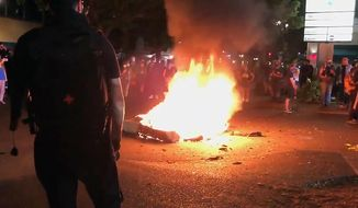 In this image taken from video a mattress burns in the street near the Portland Police Bureau's North Precinct Sunday night, Sept. 6, 2020, in Portland, Ore. Protesters have gathered for more than 100 days following the death of George Floyd in Minneapolis. (KATU Photo via AP)