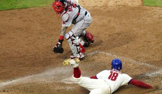 Philadelphia Phillies' Didi Gregorius, bottom, scores the the game-winning run past Boston Red Sox catcher Christian Vazquez on a two-run single by Alec Bohm off pitcher Matt Barnes during the seventh inning of the first baseball game in a doubleheader, Tuesday, Sept. 8, 2020, in Philadelphia. (AP Photo/Matt Slocum)