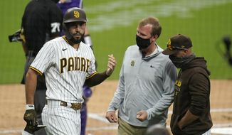 San Diego Padres' Eric Hosmer, left, reacts after injuring his hand while batting during the first inning of a baseball game against the Colorado Rockies Monday, Sept. 7, 2020, in San Diego. Padres manager Jayce Tingler, right, looks on alongside a trainer. (AP Photo/Gregory Bull)