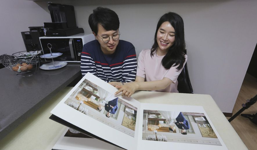 North Korean refugee Kim Seo-yun and her South Korean husband Lee Jeong-sup watch their wedding photos at their house in Seoul, South Korea Thursday, July 23, 2020. Tens of thousands of North Koreans, mostly women, have fled to South Korea over the past two decades. Arriving from a nominally socialist, extremely repressive society, these women often struggle to adjust to fast-paced, capitalistic lives in South Korea. They also face widespread discrimination, bias and loneliness. Many want to marry South Korean men, who they think will help them better adjust to new lives in South Korea. The number of these North-South Korean couples appears to be on the rise, according to at least one government survey.  (AP Photo/Ahn Young-joon)