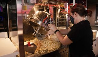An employee, who declined to give her name, makes popcorn in preparation for reopening at a Regal move theater in Irvine, Calif., Tuesday, Sept. 8, 2020. Gov. Gavin Newsom relaxed coronavirus restrictions in five more counties on Tuesday, clearing the way for restaurants, movie theaters, gyms and churches to resume indoor activities with fewer people and other modifications. (AP Photo/Jae C. Hong)