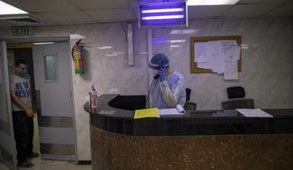 Palestinian doctors wear protective clothing as they work at the emergency room of the al-Quds Hospital in Gaza City, Monday, Sept. 7, 2020. Dozens of front-line health care workers have been infected with the novel coronavirus, dealing a new blow to overburdened hospitals. (AP Photo/Khalil Hamra)