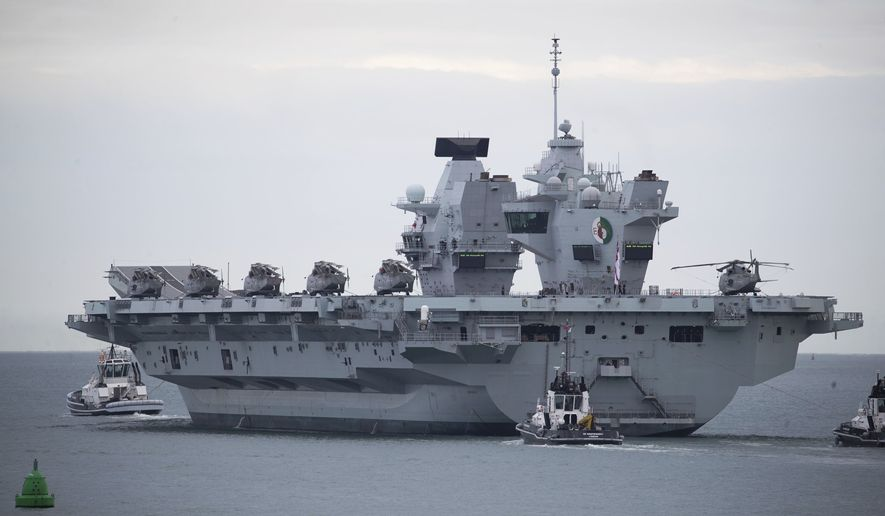 In this file photo, the British Royal Navy aircraft carrier HMS Queen Elizabeth leaves Portsmouth Naval Base as it sets sail for flight trials, Wednesday Sept. 9, 2020.  The departure comes following two days of delays caused by a small number of crew members testing positive for the coronavirus. (Andrew Matthews/PA via AP)  **FILE**