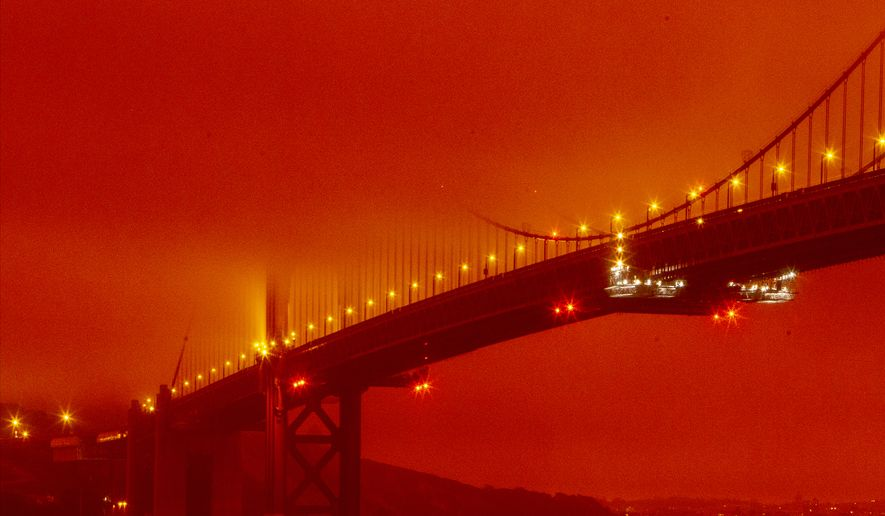 In this photo provided by Frederic Larson, the Golden Gate Bridge is seen at 11 a.m. PT, Wednesday, Sept. 9, 2020, in San Francisco, amid a smoky, orange hue caused by the ongoing wildfires. (Frederic Larson via AP)