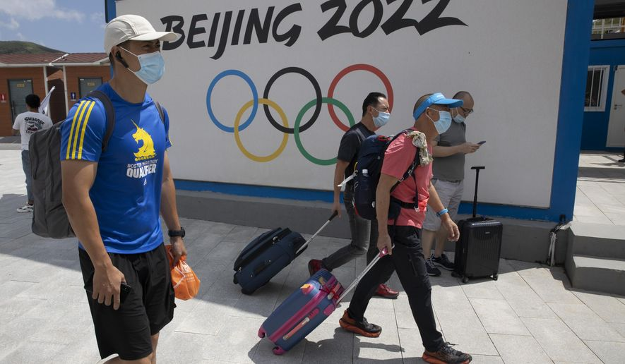 Visitors to Chongli, one of the venues for the Beijing 2022 Winter Olympics, past by the Olympics logo in Chongli in northern China's Hebei Province on Thursday, Aug. 13, 2020. China's repression in Tibet, the status of the exiled Dalai Lama, and its treatment of ethnic minorities spurred violent protests ahead of Beijing's 2008 Olympics. It could happen again. China is host to the 2022 Winter Olympics with rumblings of a boycott and calls to remove the games from Beijing because of widespread human rights violations. (AP Photo/Ng Han Guan)