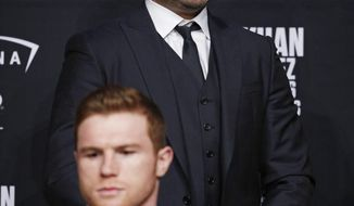 FILE- In this May 4, 2016 file photo, Oscar De La Hoya, right, attends a news conference with Canelo Alvarez at the MGM Grand, in Las Vegas. Canelo Alvarez filed a federal lawsuit Tuesday, Sept. 8, 2020, claiming breaches of contract by streaming service DAZN, Golden Boy Promotions and its CEO, Oscar De La Hoya, and seeking $280 million. (AP Photo/John Locher, File)