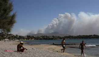 Flames burn behind the mountain as people walk next to the sea during a wildfire in Kalyvia, southeast of Athens, on Wednesday, Sept. 9, 2020. Greek firefighters, backed by water-dropping aircraft, were battling a string of wildfires near Athens and in other parts of the country Wednesday with efforts hampered by strong winds that whipped on the flames. (AP Photo/Yorgos Karahalis)