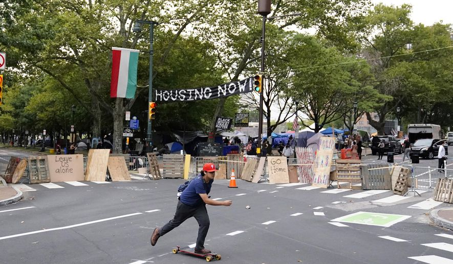 A man skateboards past a homeless encampment on the Benjamin Franklin Parkway, Wednesday, Sept. 9, 2020, in Philadelphia. City officials had ordered camp residents to leave by 9 a.m. Wednesday. (AP Photo/Matt Slocum)