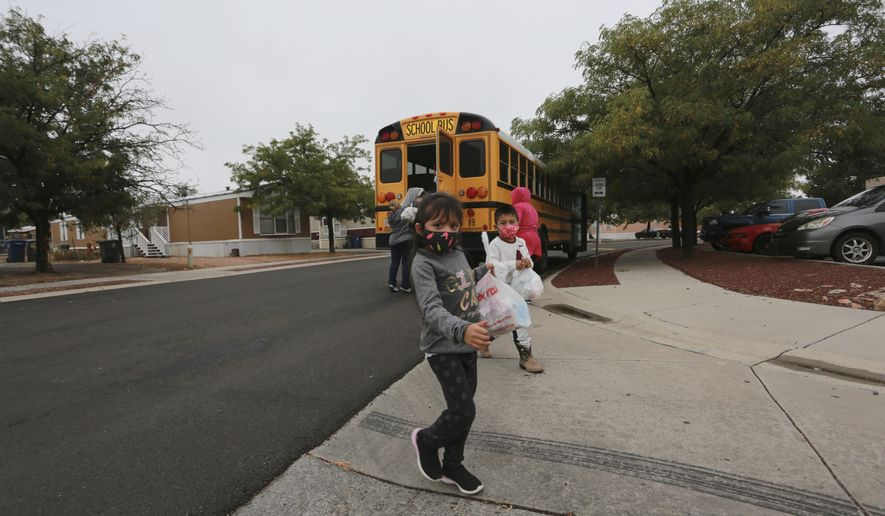 Kindergarteners who are learning remotely during the coronavirus pandemic pick up meals at a bus stop near their home on Wednesday, Sept. 9, 2020, in Santa Fe, New Mexico. The siblings were escorted by their aunt, not seen, who said she's helping her sister with childcare as the family balances work with the remote schooling schedule. (AP Photo/Cedar Attanasio)