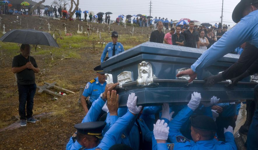 FILE - In this Sept. 29, 2017 file photo, police lift the coffin that contain the remains of a fellow officer who died while trying to cross a river in his car during the passage of Hurricane Maria, in Aguada, Puerto Rico. U.S. researchers who estimated that nearly 3,000 people died in Puerto Rico in the aftermath of Maria are now investigating deaths that might have been missed and could be linked to infrastructure damaged by the Category 4 storm, officials announced Wednesday, sept. 9, 2020.  (AP Photo/Ramon Espinosa, File)