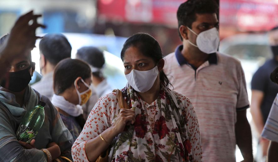 Indians wearing face masks wait for medical check-up outside a government hospital in Jammu, India, Wednesday, Sept.9, 2020. India's coronavirus cases are now the second-highest in the world and only behind the United States. (AP Photo/Channi Anand)