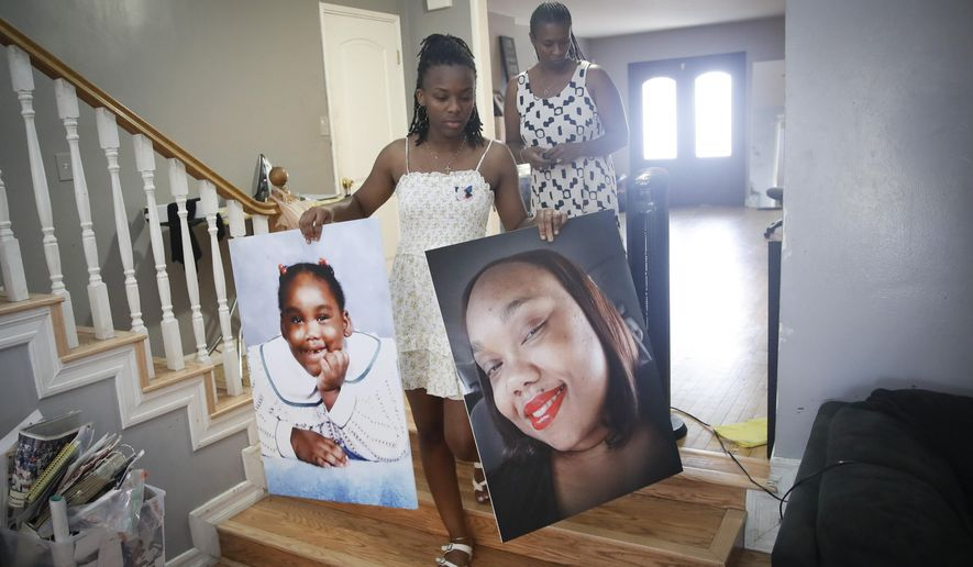 Eryanna Banks, left, carries photos of her Aunt Lydia Nunez, who died from COVID-19, in front of her mother Erika at the end of the day following a memorial service and burial for Nunez Tuesday, July 21, 2020, in Los Angeles. (AP Photo/Marcio Jose Sanchez)
