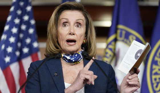 Speaker of the House Nancy Pelosi, D-Calif., holds a booklet she got from attending an event to honor the victims of 9/11 as she speaks during a news conference at the Capitol in Washington, Thursday, Sept. 10, 2020. (AP Photo/Jacquelyn Martin)