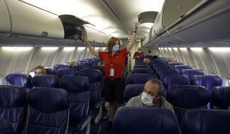 FILE - In this May 24, 2020 file photo, a Southwest Airlines flight attendant prepares a plane bound for Orlando, Fla. for takeoff at Kansas City International airport in Kansas City, Mo. Airline workers are making a last-ditch push for $25 billion in federal money to avoid furloughs for six more months. But critics including some lawmakers say the airlines need to shrink because fewer people are traveling.  (AP Photo/Charlie Riedel, File)