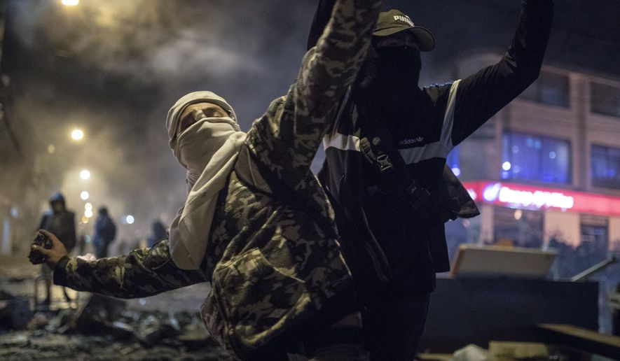 A masked and hooded man hurls stones at police during protests sparked by the death of a man after he was detained by police for violating social distancing rules to curb the spread of the coronavirus in Bogota, Wednesday, Sept. 9, 2020. Javier Ordonez died in a hospital after receiving repeated electric shocks with a stun gun from officers who detained him, seen on a video taken by Ordonez's friend, and published on social media. (AP Photo/Ivan Valencia)