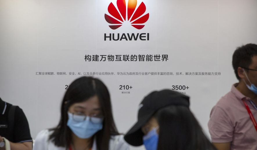 Visitors wearing face masks to protect against the coronavirus stand at a booth for Chinese technology firm Huawei at the China International Fair for Trade in Services (CIFTIS) in Beijing, Saturday, Sept. 5, 2020. Recent U.S. sanctions on Huawei Technologies have left the company without enough computer chips, hurting the growth of its smartphone business, a top executive says. (AP Photo/Mark Schiefelbein)