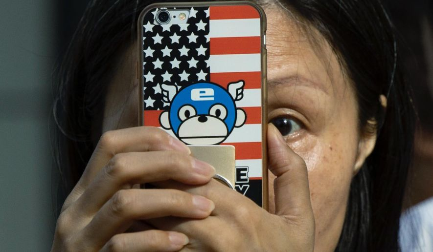 FILE - In this July 26, 2020, file photo, a woman takes a photo with a phone that has a United States flag themed cover outside the United States Consulate in Chengdu in southwest China's Sichuan province. China is delaying the renewal of press cards for at least five journalists working at four U.S. media outlets, an organization of foreign correspondents said Monday, Sept. 7, 2020 making them vulnerable to expulsion in apparent retribution for Washington's targeting of Chinese reporters working in the United States. (AP Photo/Ng Han Guan, File)