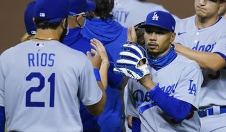 Los Angeles Dodgers' Mookie Betts, right, celebrates with Edwin Rios (21) and others after the Dodgers' 6-4 win over the Arizona Diamondbacks in 10 innings in a  baseball game Wednesday, Sept. 9, 2020, in Phoenix. (AP Photo/Ross D. Franklin)