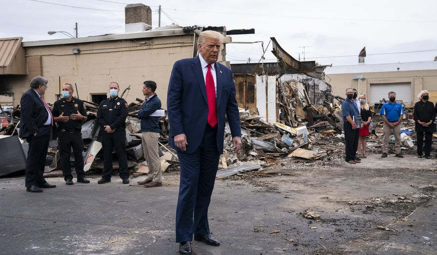 """FILE - In this Sept. 1, 2020 file photo, President Donald Trump tours an area damaged during demonstrations after a police officer shot Jacob Blake in Kenosha, Wis. Wisconsin Democrats, stung by President Trump's narrow win four years ago, are confident the lessons they learned will ensure he doesn't do it again. But Republicans say civil unrest that followed a police shooting in Kenosha, and Trump's """"law and order"""" message, will help him win over the crucial white suburban voters he needs to capture a second term. (AP Photo/Evan Vucci File)"""