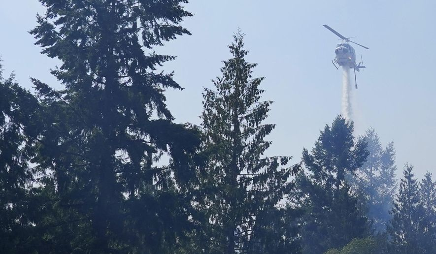 A helicopter makes a water drop, Wednesday, Sept. 9, 2020, on a hotspot of a wildfire burning in Bonney Lake, Wash., south of Seattle. (AP Photo/Ted S. Warren, Pool)