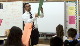 """FILE - In this May 8, 2018, file photo, Atif Qarni, Virginia's Secretary of Education, demonstrates to fifth graders in James Taylor Monterey Elementary School class, how to cut construction paper to form a T-shirt, as part of a lesson focusing on """"leadership"""" qualities in Roanoke, Va. Parents at Thomas Jefferson High School for Science and Technology, an elite northern Virginia high school ,are fighting  efforts from Virginia Secretary of Education Atif Qarni, who organized a task force to evaluate diversity issues at TJ and 18 other magnet schools in Virginia designated as """"Governor's Schools."""" (Stephanie Klein-Davis/The Roanoke Times via AP)"""