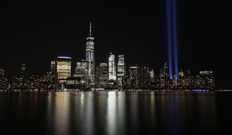In this Sept. 11, 2017, file photo, the Tribute in Light illuminates in the sky above the Lower Manhattan area of New York, as seen from across the Hudson River in Jersey City, N.J. The coronavirus pandemic has reshaped how the U.S. is observing the anniversary of 9/11. The terror attacks' 19th anniversary will be marked Friday, Sept. 11, 2020, by dueling ceremonies at the Sept. 11 memorial plaza and a corner nearby in New York. (AP Photo/Jason DeCrow, File)
