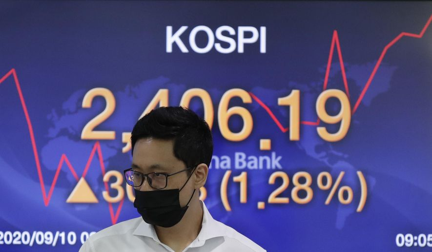 A currency trader walks by the screen showing the Korea Composite Stock Price Index (KOSPI) at the foreign exchange dealing room in Seoul, South Korea, Thursday, Sept. 10, 2020. Asian stock markets gained Thursday after Wall Street rebounded from a three-day slump for tech stocks. (AP Photo/Lee Jin-man)