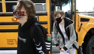 Sophomores Hunter Keith, left, and Carson Anderson get off the bus on the first day of in-person instruction at Jenks High School, Thursday, Sept. 10, 2020, amid the coronavirus pandemic, in Tulsa, Okla. (Mike Simons/Tulsa World via AP)