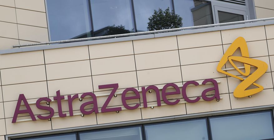 FILE - This Saturday, July 18, 2020 file photo shows a general view of AstraZeneca offices and the corporate logo in Cambridge, England. Late stage trials into a coronavirus vaccine developed by Oxford University and drugmaker AstraZeneca were paused after a woman who received the experimental shot developed severe neurological symptoms, a spokesman for the pharmaceutical said Thursday, Sept. 10, 2020. (AP Photo/Alastair Grant, file)