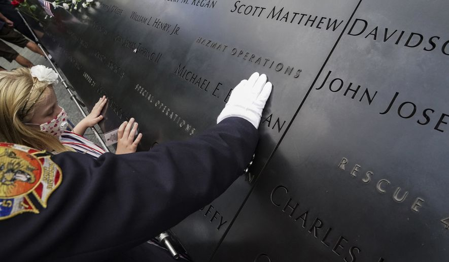 Matthew Cook places his hand on the inscribed names of the deceased at the National September 11 Memorial and Museum, Friday, Sept. 11, 2020, in New York. Americans will commemorate 9/11 with tributes that have been altered by coronavirus precautions and woven into the presidential campaign. (AP Photo/John Minchillo)