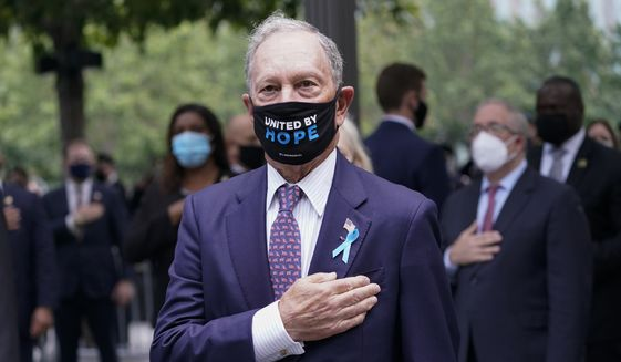 Former New York City Mayor Michael Bloomberg stands for the pledge of allegiance during a ceremony marking the 19th anniversary of the 9/11 terrorist attacks at the National September 11 Memorial & Museum, Friday, Sept. 11, 2020, in New York. (AP Photo/Mary Altaffer)